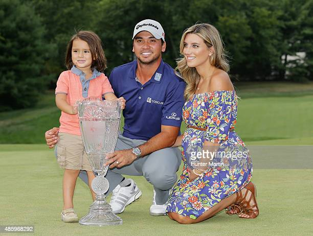 Jason Day of Australia poses with the winner's trophy on the 18th green alongside his son Dash and wife Ellie after his sixstroke victory at The...