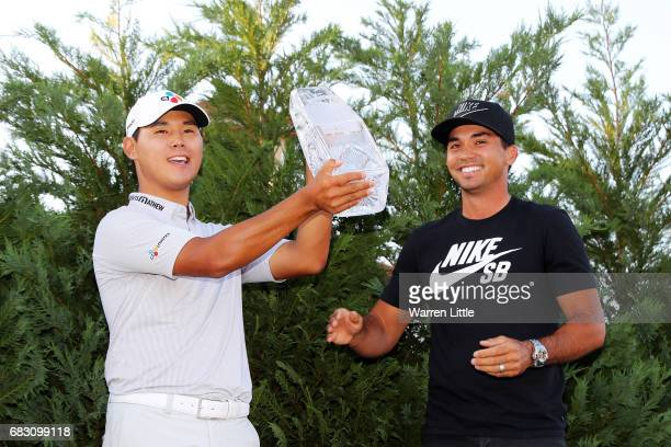 Jason Day of Australia presents the winner's trophy to Si Woo Kim of South Korea after the final round of THE PLAYERS Championship at the Stadium...