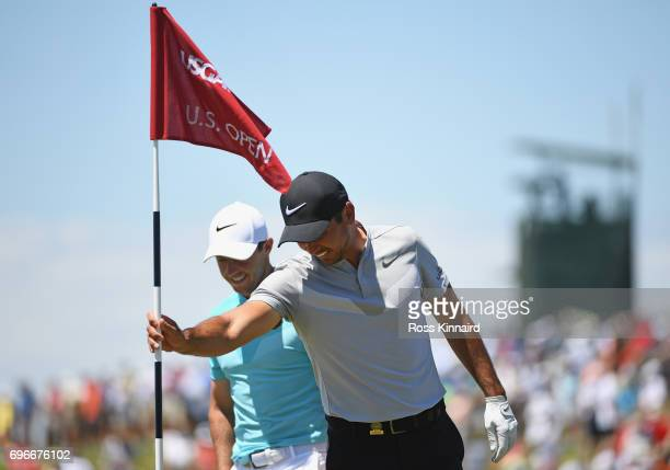 Jason Day of Australia pulls the flag on the ninth green as Rory McIlroy of Northern Ireland looks on during the second round of the 2017 US Open at...