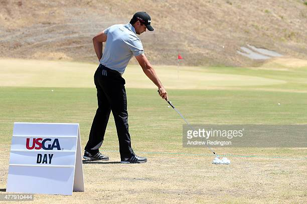 Jason Day of Australia reaches for a golf ball on the practice ground during the third round of the 115th US Open Championship at Chambers Bay on...