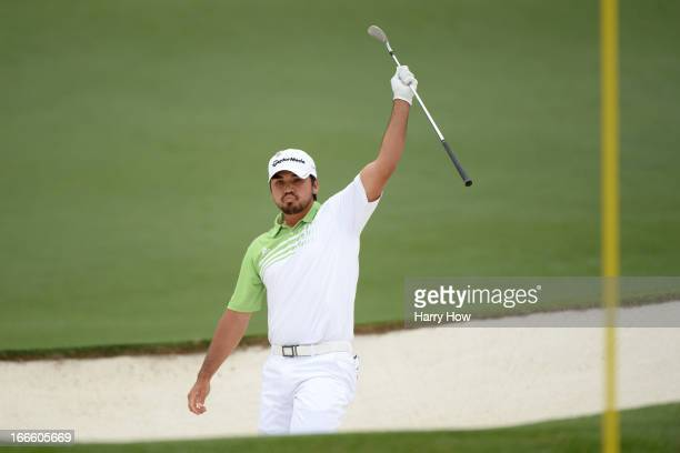 Jason Day of Australia reacts after hitting the ball out of the bunker for an eagle on the second hole during the final round of the 2013 Masters...