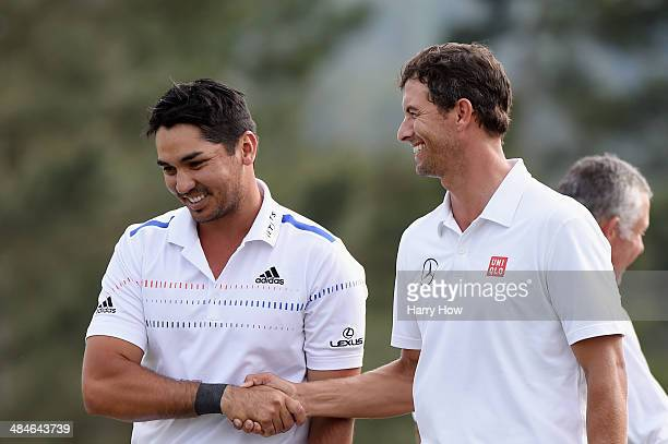 Jason Day of Australia shakes hands with Adam Scott of Australia on the 18th hole during the final round of the 2014 Masters Tournament at Augusta...
