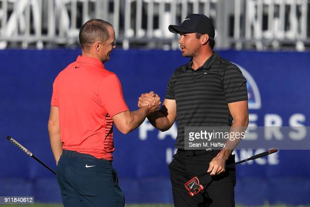 Jason Day of Australia shakes hands with Alex Noren of Sweden on the sixth playoff on the 18th green after winning the Farmers Insurance Open at...