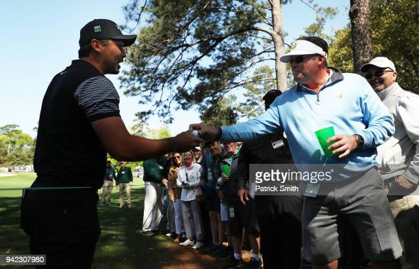 Jason Day of Australia talks with a patron after his shot landed in the patron's beverage during the first round of the 2018 Masters Tournament at...