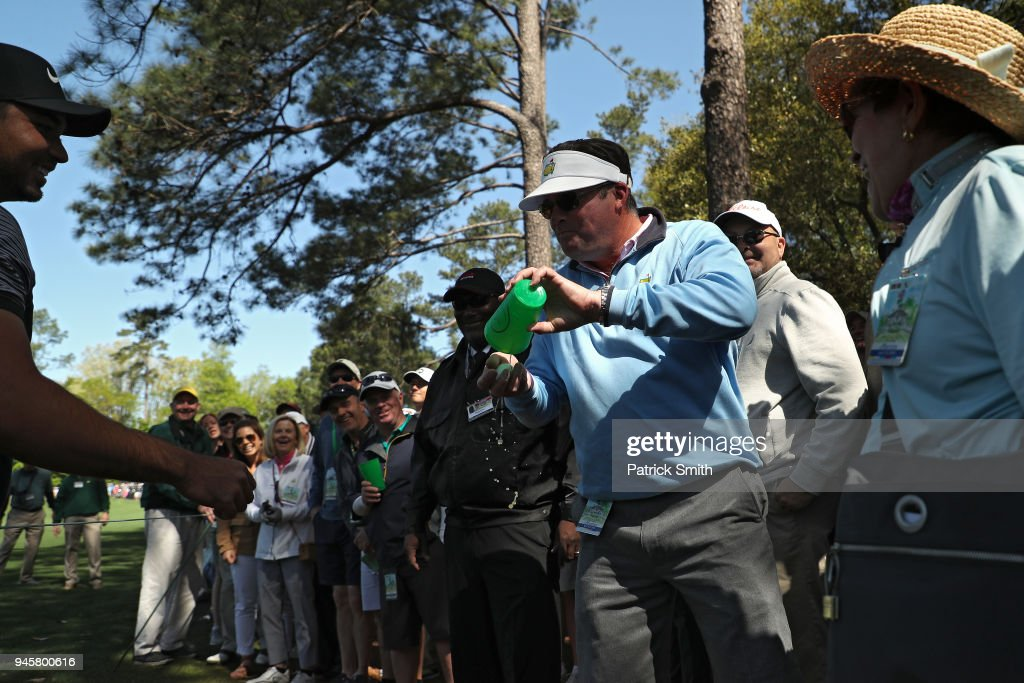 Jason Day of Australia talks with a patron after his shot landed in the patron's beverage during the first round of the 2018 Masters Tournament at Augusta National Golf Club on April 5, 2018 in Augusta, Georgia.