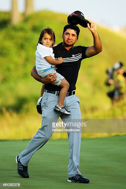 Jason Day of Australia walks off the 18th green with his son Dash after winning the 2015 PGA Championship with a score of 20under par at Whistling...