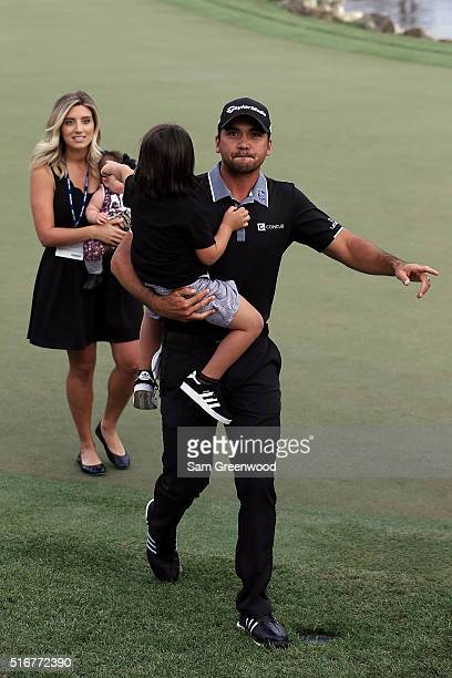 Jason Day of Australia walks off the 18th green with his wife Ellie and children Dash and Lucy following the final round of the Arnold Palmer...