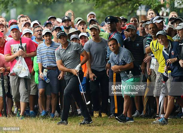 Jason Day of Australia watches his shot from the trees on the 17th hole during the continuation of the weather delayed third round of the 2016 PGA...