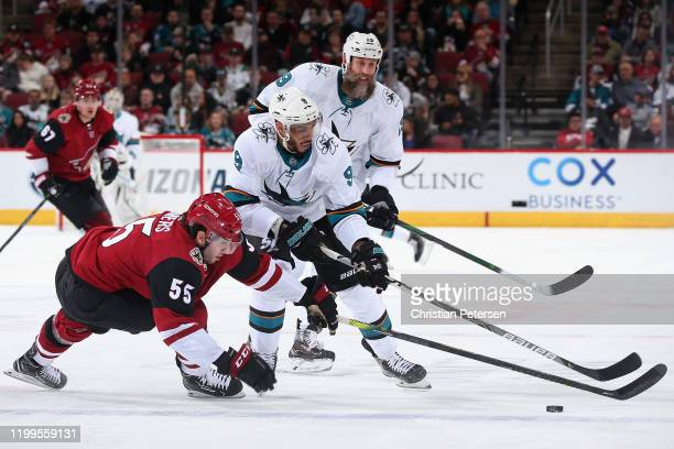Jason Demers of the Arizona Coyotes attempts to clear the puck from Evander Kane and Joe Thornton of the San Jose Sharks during the second period of...