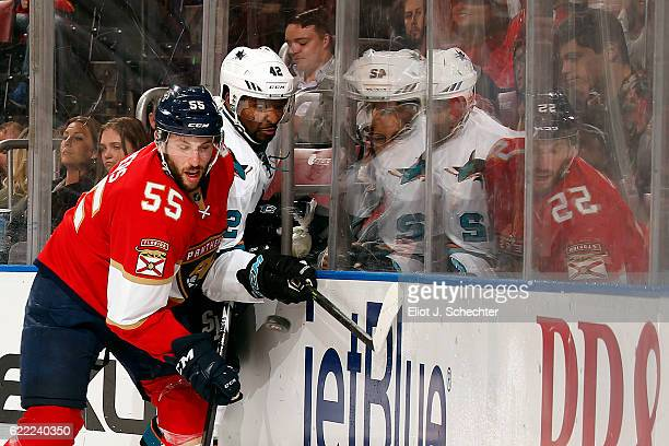 Jason Demers of the Florida Panthers checks Joel Ward of the San Jose Sharks into the boards during second period action at the BBT Center on...