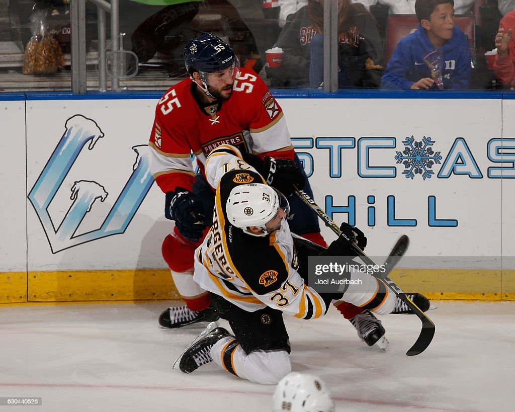 Jason Demers #55 of the Florida Panthers checks Patrice Bergeron #37 of the Boston Bruins at the BB&T Center on December 22, 2016 in Sunrise, Florida. The Bruins defeated the Panthers 3-1.