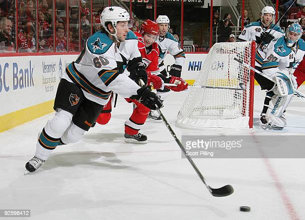 Jason Demers of the San Jose Sharks defends the puck against Erik Cole of the Carolina Hurricanes on November 1, 2009 at the RBC Center in Raleigh,...
