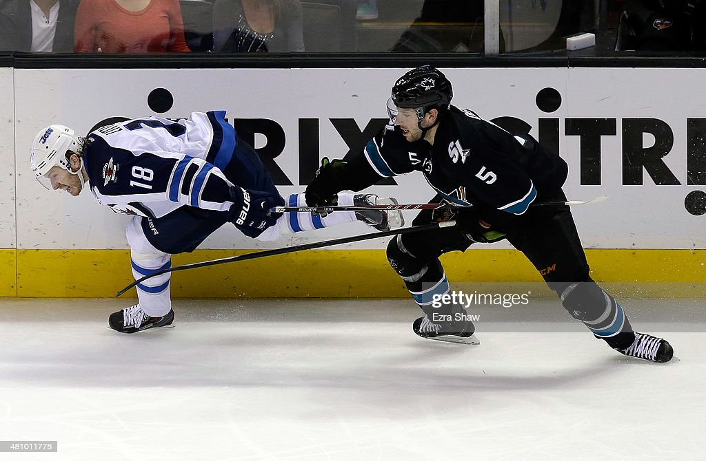 Jason Demers #5 of the San Jose Sharks gets tangled up with Bryan Little #18 of the Winnipeg Jets at SAP Center on March 27, 2014 in San Jose, California.