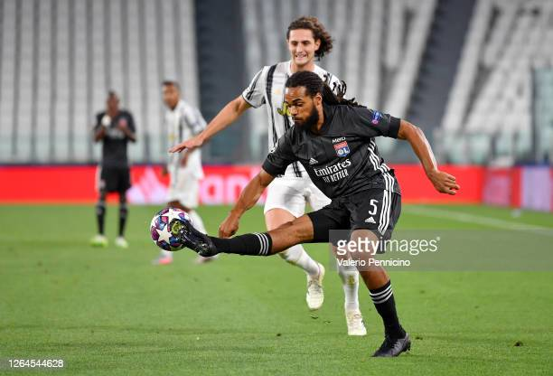 Jason Denayer of Olympique Lyon controls the ball under pressure from Adrien Rabiot of Juventus during the UEFA Champions League round of 16 second...