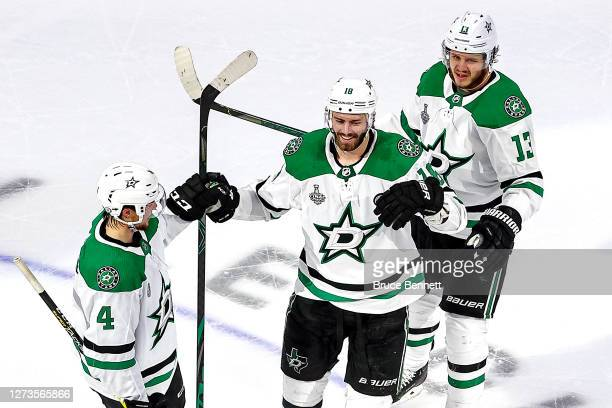 Jason Dickinson of the Dallas Stars is congratulated by Miro Heiskanen and Mattias Janmark after scoring an emptynet goal against the Tampa Bay...