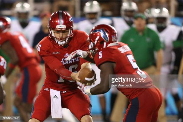 Jason Driskel hands the ball off to Devin Singletary of the Florida Atlantic Owls during third quarter action against the Marshall Thundering Herd at...