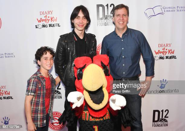 Jason Drucker Charlie Wright and Jeff Kinney pose with Harry The Hawk at Diary Of A Wimpy Kid The Long Haul Atlanta screening hosted by Dwight Howard...