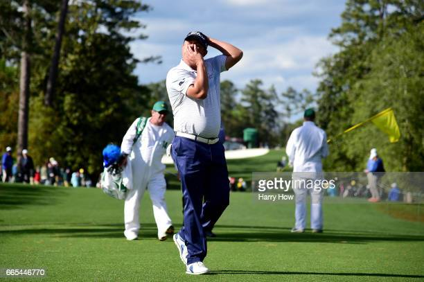 Jason Dufner of the United States adjusts his neck as he walks to the 18th tee during the first round of the 2017 Masters Tournament at Augusta...