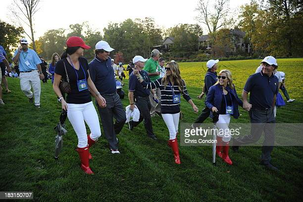 Jason Dufner of the US Team fist bump Nadine Moze as Amanda Dufner Amy Mickelson and Phil Mickelson looks on during the Day One FourBall Matches of...