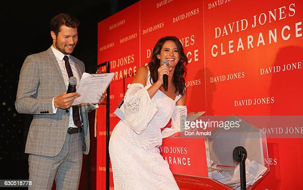 Jason Dundas and Jesinta Campbell read the results of a lottery outside the David Jones Elizabeth St tore just prior to opening during the Boxing Day...