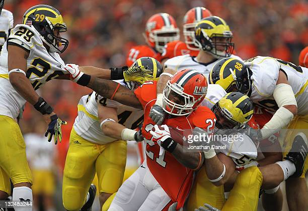 Jason Ford of the Illinois Fighting Illini grabs Troy Woolfolk of the Michigan Wolverines as he is tackled by Desmond Morgan, Ryan Van Bergen and...