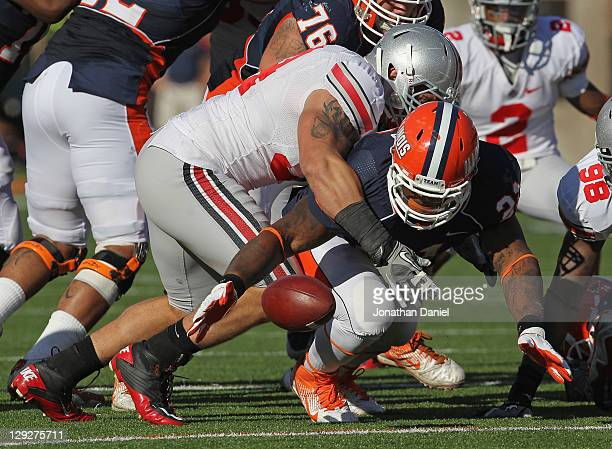 Jason Ford of the Illinois Fighting Illini moves to recover his own fumble as he is hit by John Simon of the Ohio State Buckeyes at Memorial Stadium...