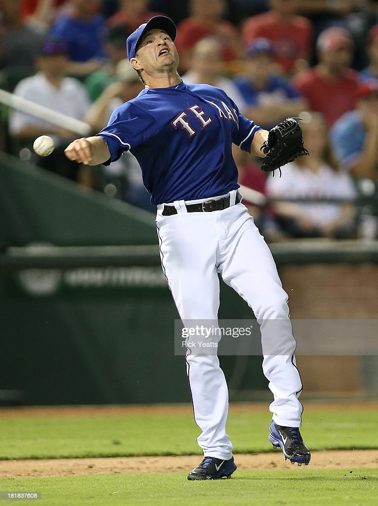 Jason Frasor #44 of the Texas Rangers recovers a short infield hit by Matt Dominguez #30 of the Houston Astros throwing Dominguez out at first base at Rangers Ballpark in Arlington on September 25, 2013 in Arlington, Texas.