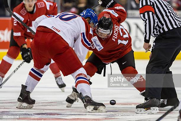 Jason Fuchs of Switzerland battles for the puck against David Kampf of Czech Republic during the 2015 IIHF World Junior Championship on December 27...