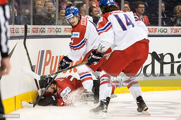 Jason Fuchs of Switzerland is checked into the boards by Jan Scotka of Czech Republic during the 2015 IIHF World Junior Championship on December 27...
