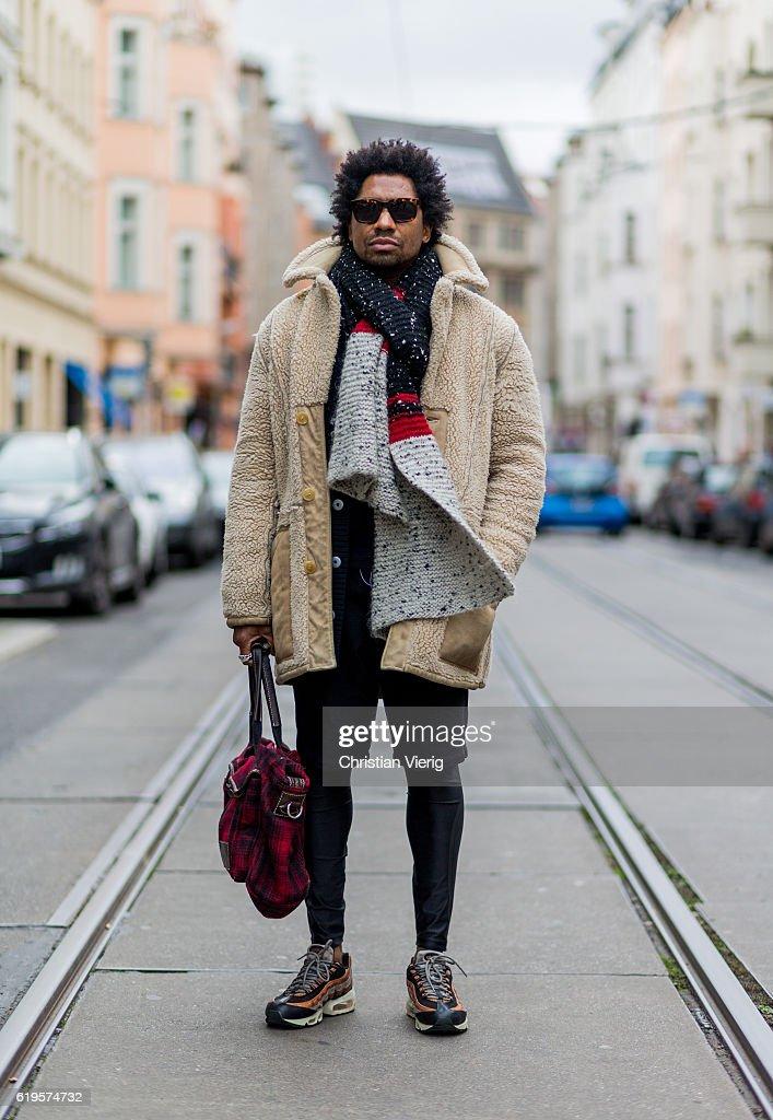 Jason Fulton wears an oversized black, red, dark white scarf, a creme wool coat, red plaid weekender bag, black shorts, black leggings, Air Max sneaker and sunglasses on October 31, 2016 in Berlin, Germany.