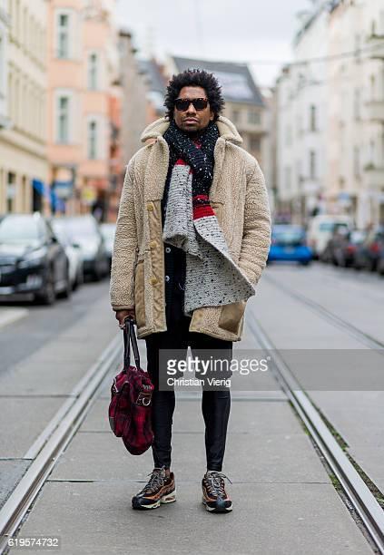 Jason Fulton wears an oversized black red dark white scarf a creme wool coat red plaid weekender bag black shorts black leggings Air Max sneaker and...