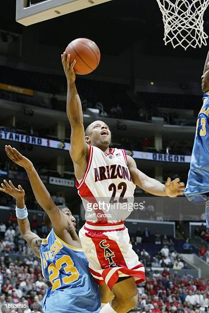 Jason Gardner of Arizona shoots a layup between Andre Patterson and TJ Cummings of UCLA during overtime of the Pac10 tournament game on March 13 2003...