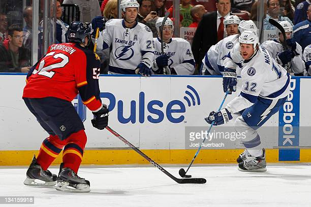 Jason Garrison of the Florida Panthers defends the zone as Ryan Malone of the Tampa Bay Lightning skates over the blue line with the puck on November...