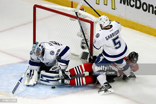 Jason Garrison of the Tampa Bay Lightning checks Jonathan Toews of the Chicago Blackhawks into the net during Game Four of the 2015 NHL Stanley Cup...