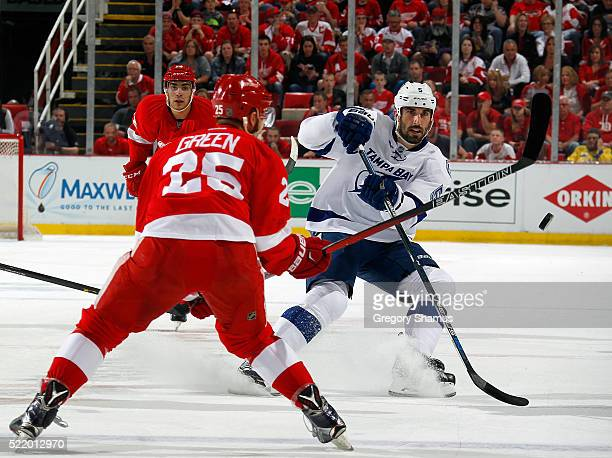Jason Garrison of the Tampa Bay Lightning passes the puck past the stick of Mike Green of the Detroit Red Wings during the first period of Game Three...