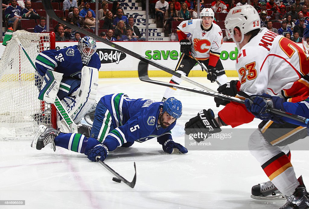 Jason Garrison #5 of the Vancouver Canucks bats the puck away from Sean Monahan #23 of the Calgary Flames in front of Jacob Markstrom #35 of the Vancouver Canucks during their NHL game at Rogers Arena April 13, 2014 in Vancouver, British Columbia, Canada. Vancouver won 5-1.