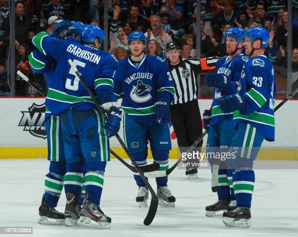 Jason Garrison of the Vancouver Canucks is congratulated by teammates Daniel Sedin Henrik Sedin and Jannik Hansen after scoring against the Anaheim...