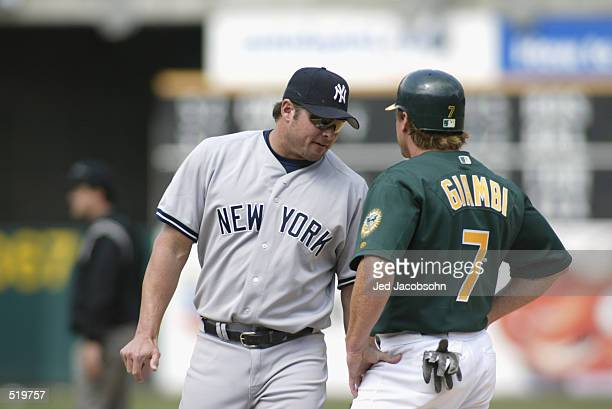 Jason Giambi of the New York Yankees chats with brother Jeremy Giambi of the Oakland A's during the game at Network Associates Coliseum in Oakland...