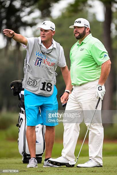 Jason Gore checks yardage with his caddie before teeing off on the second hole during the third round of the Webcom Tour Championship at TPC Sawgrass...