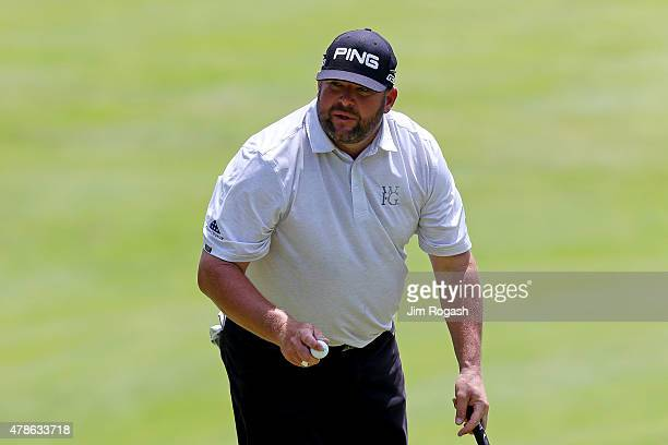 Jason Gore holds up his ball after finishing on the 18th green during the second round of the Travelers Championship at TPC River Highlands on June...