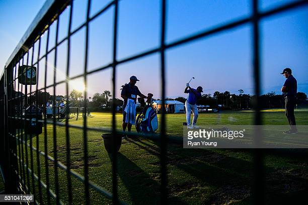 Jason Gore warms up on the practice range as the sun rises during the first round of THE PLAYERS Championship on THE PLAYERS Stadium Course at TPC...