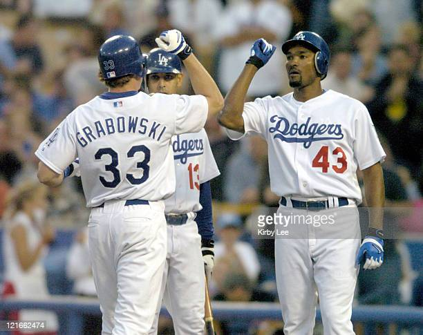 Jason Grabowski of the Los Angeles Dodgers is greeted by Alex Cora and Juan Encarnacion after a tworun home in the second inning of 73 victory over...