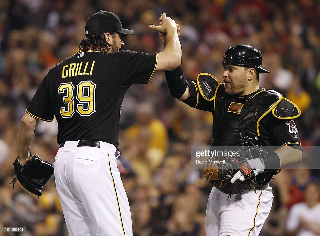 Jason Grilli #39 of the Pittsburgh Pirates celebrates with catcher Russell Martin #55 after the final out of the game against the Cincinnati Reds on September 21, 2013 at PNC Park in Pittsburgh Pennsylvania. The Pirates defeated the Reds 4-2.
