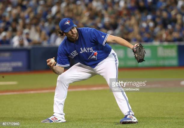 Jason Grilli of the Toronto Blue Jays fields the baseball but cannot throw out Jose Peraza of the Cincinnati Reds who hits a soft infield single in...