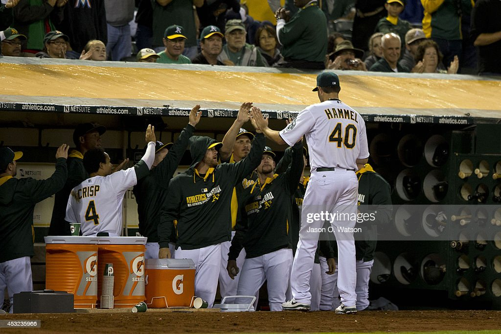 Jason Hammel #40 of the Oakland Athletics is congratulated by teammates in the dugout after being relieved against the Tampa Bay Rays during the sixth inning at O.co Coliseum on August 5, 2014 in Oakland, California.