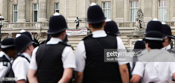 Jason Hatch, a Fathers 4 Justice campaigner, dressed as Batman protests on the balcony at Buckingham Palace as British police officers look on on...