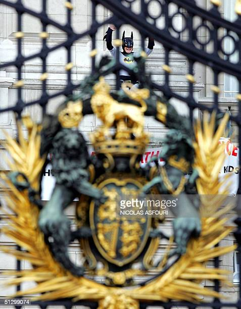 Jason Hatch is seen through the gates of Buckingham Palace after scaling the facade in London, 13 September 2004. Hatch a member of the group...