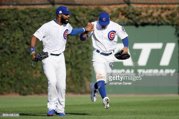 Jason Heyward and Jon Jay of the Chicago Cubs celebrate after Jay caught a fly ball in the fourth inning against the Washington Nationals during game...