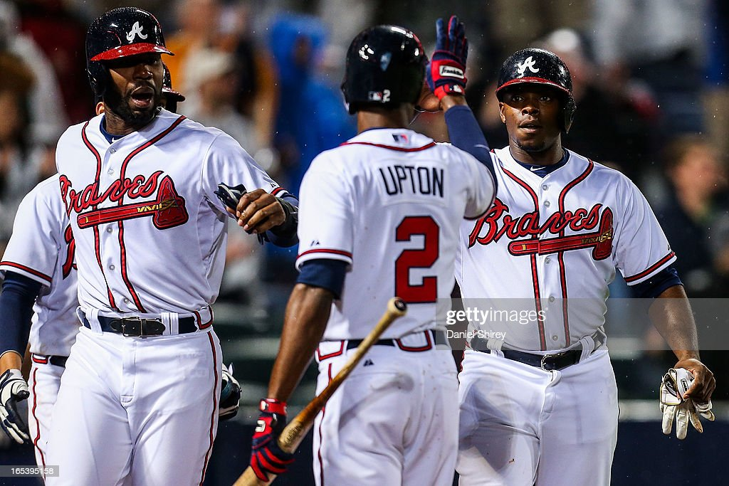 Jason Heyward #22 and Justin Upton #8 of the Atlanta Braves celebrate with B.J. Upton #2 after scoring runs in the fourth inning of the game against the Philadelphia Phillies at Turner Field on April 3, 2013 in Atlanta, Georgia.