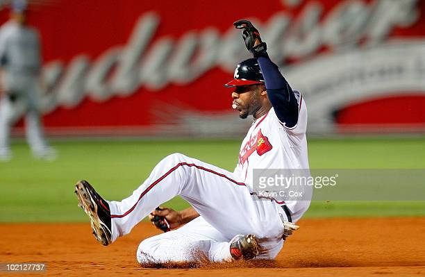 Jason Heyward of the Atlanta Braves blows a bubble as he slides safely into third base against the Tampa Bay Rays at Turner Field on June 15 2010 in...